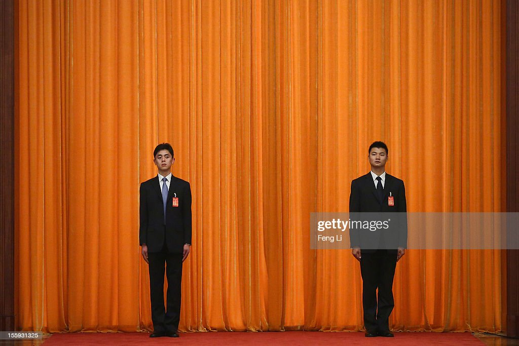 Two soldiers dressed as ushers guard in front of a curtain during a meeting of the opening session of the 18th Communist Party Congress at the Great Hall of the People on November 9, 2012 in Beijing, China. The Communist Party Congress will convene from November 8-14 and will determine the party's next leaders.