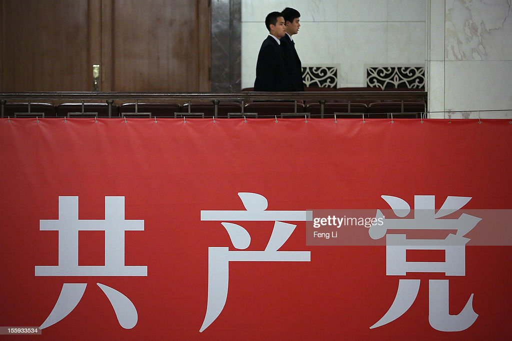 Two soldiers dressed as ushers pass the banner displaying the words 'Communist Party' during a meeting of the 18th Communist Party Congress at the Great Hall of the People on November 9, 2012 in Beijing, China. The Communist Party Congress will convene from November 8-14 and will determine the party's next leaders.