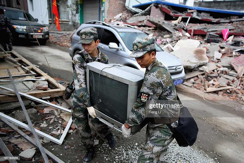 Two soldiers help survivors to move out the television set from their damaged house on April 22, 2013 in Baoxing county of Ya An, China. A magnitude 7 earthquake hit China's Sichuan province on April 20 claiming over 190 lives and injuring thousands.