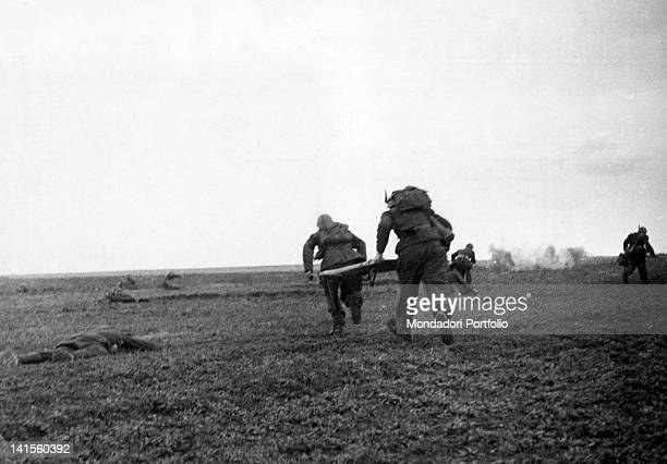 Two soldiers of the Italian Alpine Troops of 'Monte Cervino' battalion rushing to help wounded soldiers Klinovj June 1942
