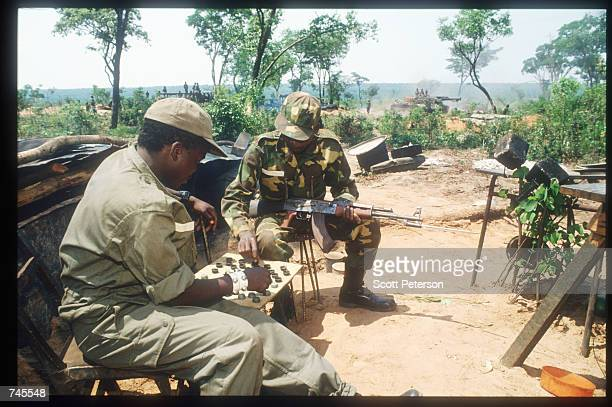 Two soldiers play checkers October 25 1993 in Menogue Angola Angolan rebels have continued the civil war after losing elections on September 29 1992