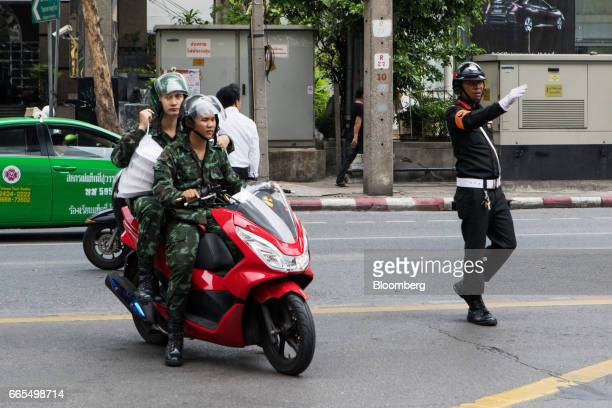Two soldiers ride a motorcycle in the Phaya Thai District of Bangkok Thailand on Wednesday April 5 2017 The central bank predicts growth will...