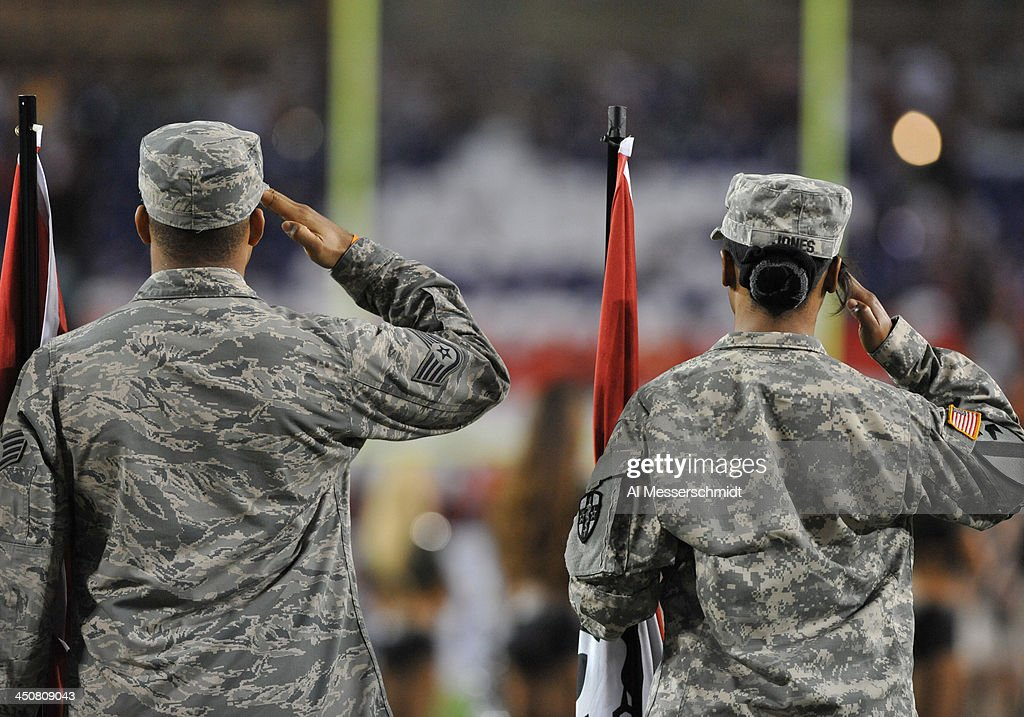 Two soldiers salute during military appreciation night as the Miami Dolphins play against the Tampa Bay Buccaneers in an ESPN Monday Night Football game November 11, 2013 at Raymond James Stadium in Tampa, Florida. Tampa won 22 - 19.