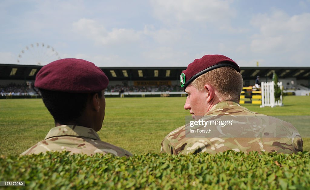 Two soldiers sit and watch the horsejumping events at the Great Yorkshire Show on July 9, 2013 in Harrogate, England. The Great Yorkshire Show is the UK's premier agricultural event and brings together agricultural displays, livestock events, farming demonstrations, food, dairy and produce stands as well as equestrian events to thousands of visitors over the three days.