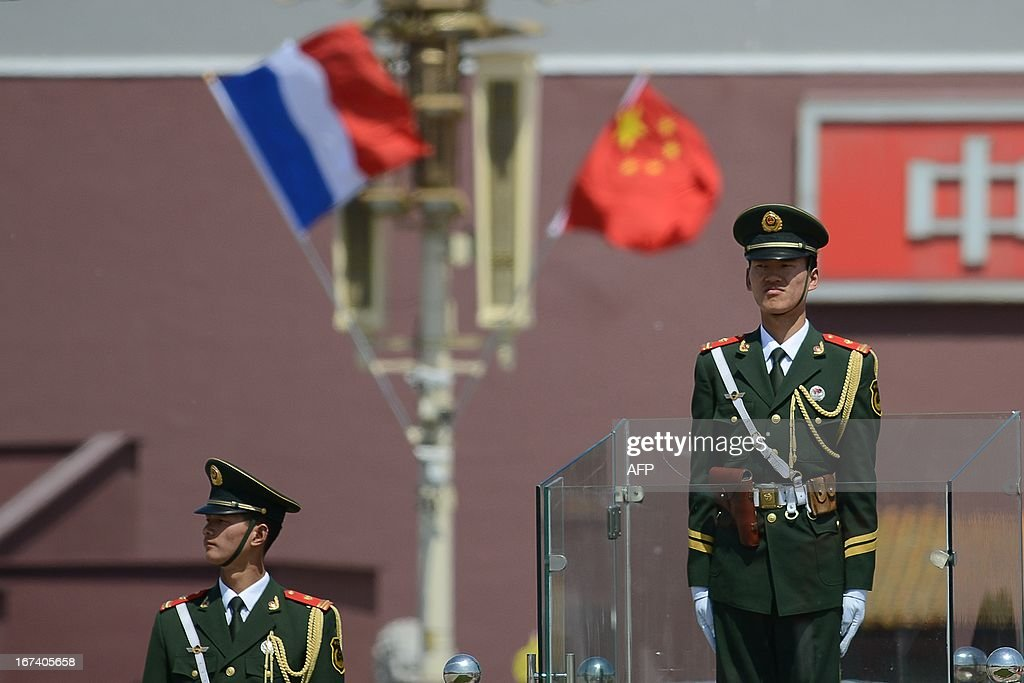 Two soldiers stand guard in front of a French (L) and Chinese national flag (R) at Tiananmen square in Beijing on April 25, 2013. French President Francois Hollande arrived in Beijing on April 25 on a trip aimed at boosting exports to China, with hopes that deals can be reached over the sale of aircraft and nuclear power.