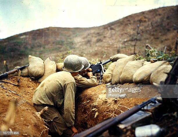Two soldiers train their 30 caliber machine gun on Communist positions on the western front during the Korean War July 1952