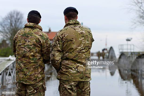 Two soldiers walk across Cawood Bridge which crosses the River Ouse on December 28 2015 in Cawood England Heavy rain over the Christmas period has...