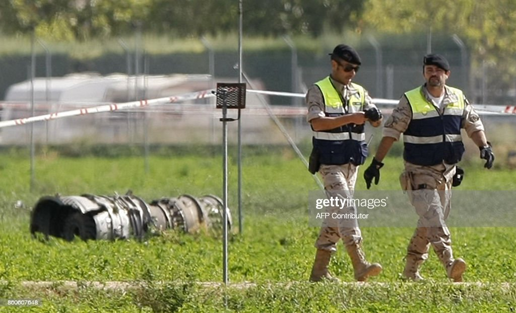 Two soldiers walk past wreckache of a crashed Eurofighter plane near a military base at Albacete, 300 kilometres (180 miles) southeast of Madrid on October 12, 2017. A Spanish Eurofighter jet crashed today after taking part in a military display in Madrid for Spain's national day, killing its pilot, the defence ministry said. PHOTO / Luis VIZCAINO