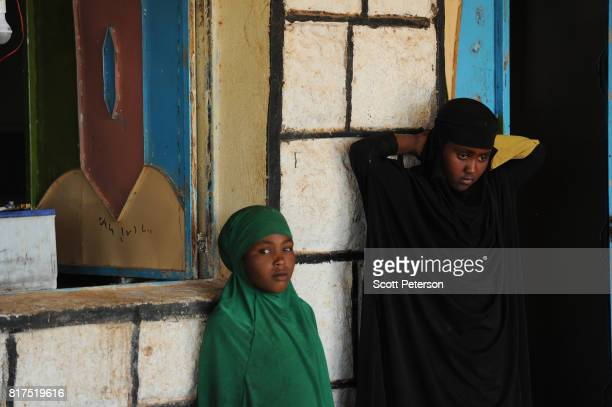 Two Somali girls watch as villagers who have benefited from food and cash donations mobilized by a WhatsApp group called 'Daryeel' formed by diaspora...
