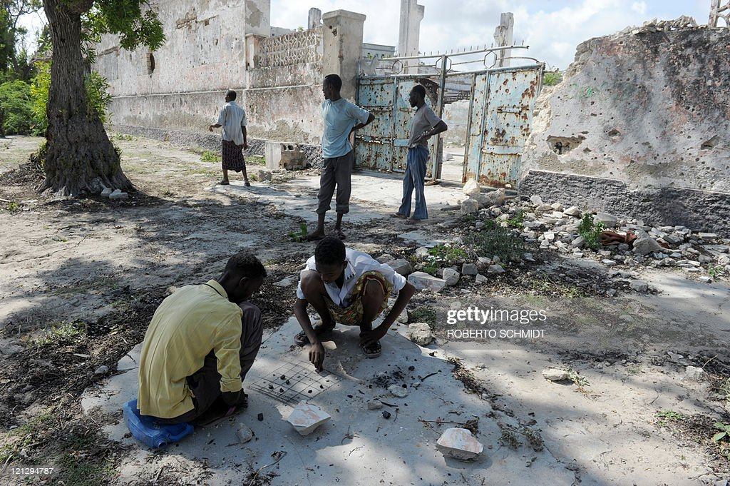 Two Somali men play a game of Shax on a broken sidewalk in one of the the oldest neighborhoods of Mogadishu on August 17, 2011. This neighborhood used to be one of the finest in the city and housed some of the fanciest houses in the 70's and 80's decade. Two decades of armed struggle that began in 1991 has reduced large parts of the city to rubble. Currently, the Somali Federal Transitional Government (TFG) is in power with the help of a 9,000 soldier strong contingent of the African Union and is battling the Al-Shebab, an Al-Qeada affiliated radical Islamist group.