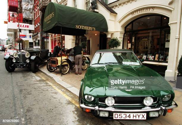 Two Sotheby's employees position a 1903 Humberette 5hp twoseater in the entrance of their headquarters in London this morning alongside a 1931...