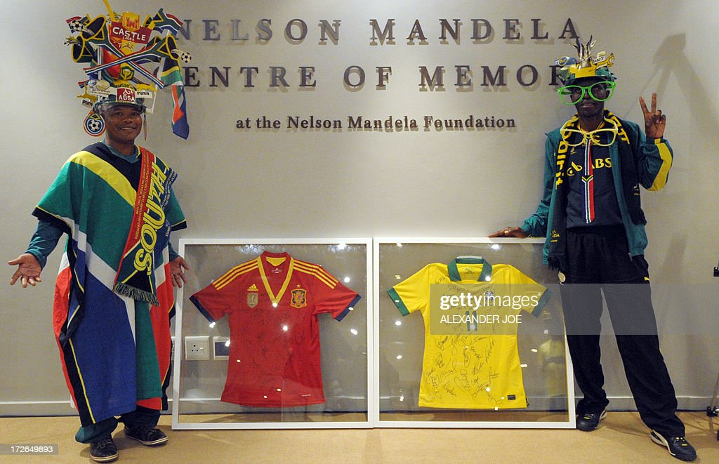 Two South African football fans wearing makarapas pose on July 4 2013 near a Brazilian football team jersey with players' autographs and messages...