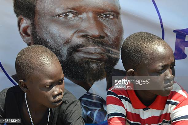 Two South Sudanese boys wait from the arrival of South Sudan's President Salva Kiir Mayardit at the airport in Juba on August 10 2014 Warring rivals...