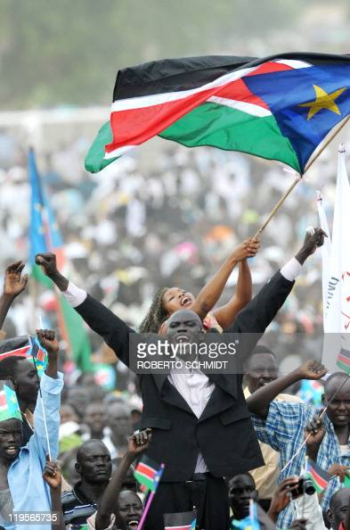 Two Southern Sudan residents wave flags as they celebrate the independance of the south from the north during a ceremony in the capital Juba on July...