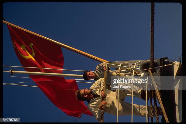 Two Soviet Union sailors stand under their flag on a training ship's bow Seattle Washington USA
