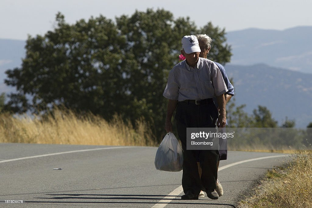 Two Spanish pensioners walk along a roadside in Becedas, Spain, on Thursday, Sept. 26, 2013. Prime Minister Mariano Rajoy is increasingly dependent on the pension reserve fund as it reaps lower returns on Spanish sovereign debt, which comprise 97.5 percent of its investments. Photographer: Antonio Heredia/Bloomberg via Getty Images