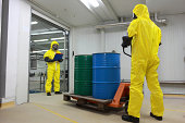 Two specialists in protective uniforms dealing with barrels with toxic substance