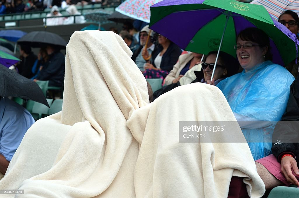 Two spectators cover themselves in a blanket as rain stops play on the fifth day of the 2016 Wimbledon Championships at The All England Lawn Tennis Club in Wimbledon, southwest London, on July 1, 2016. / AFP / GLYN