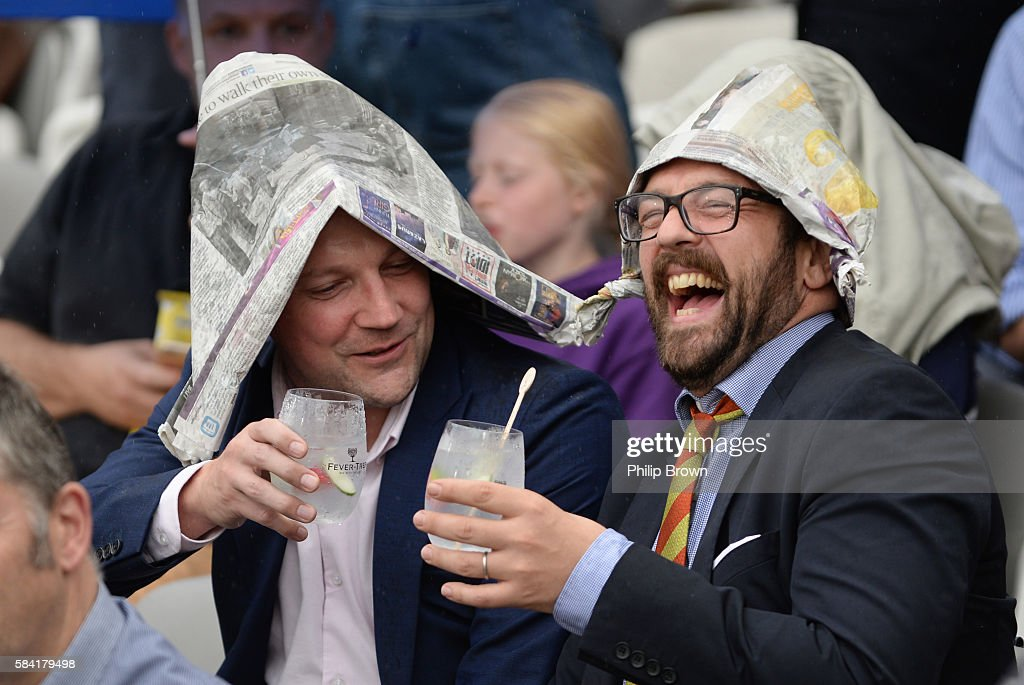 Two spectators enjoy themselves as rain delayed the start of the Natwest T20 Blast match between Middlesex and Essex at Lord's cricket ground on July...