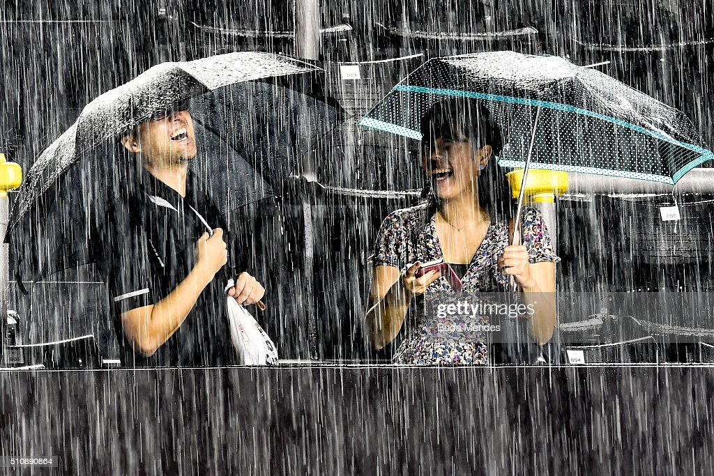 Two spectators wait in the stands as rain suspends the match between David Ferrer of Spain and Albert Ramos-Vinolas of Spain during the Rio Open at Jockey Club Brasileiro on February 17, 2016 in Rio de Janeiro, Brazil.