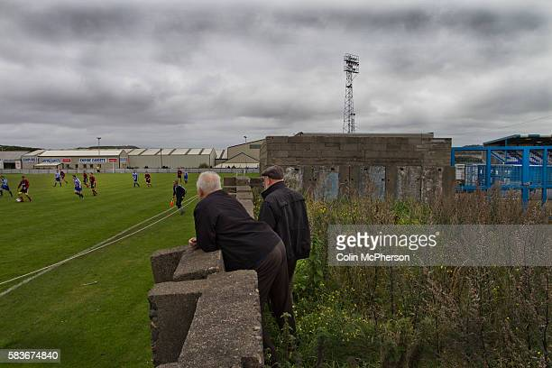 Two spectators watching West Lancashire Football League Furness Rovers playing on their Strawberry fields pitch adjacent to Barrow AFC's Furness...