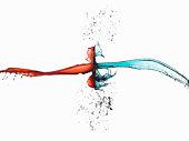 Two splashes of colored liquid colliding, studio shot