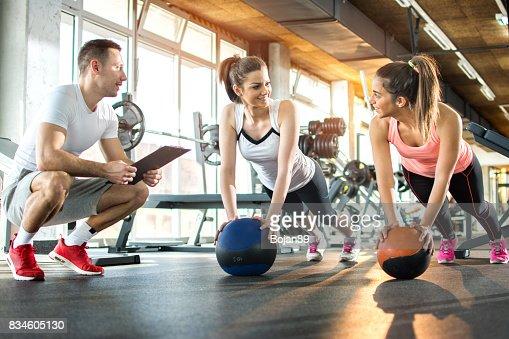 Zwei sportliche Mädchen trainieren Fitness Bälle zwar ihre Fitness-Trainer, die Verfolgung der Fortschritte auf Zwischenablage. : Stock-Foto