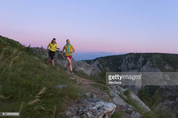 Two sporty women with headlamps trail running in the dusk