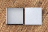 Two white square boxes opened and closed on wood background. 3d illustration