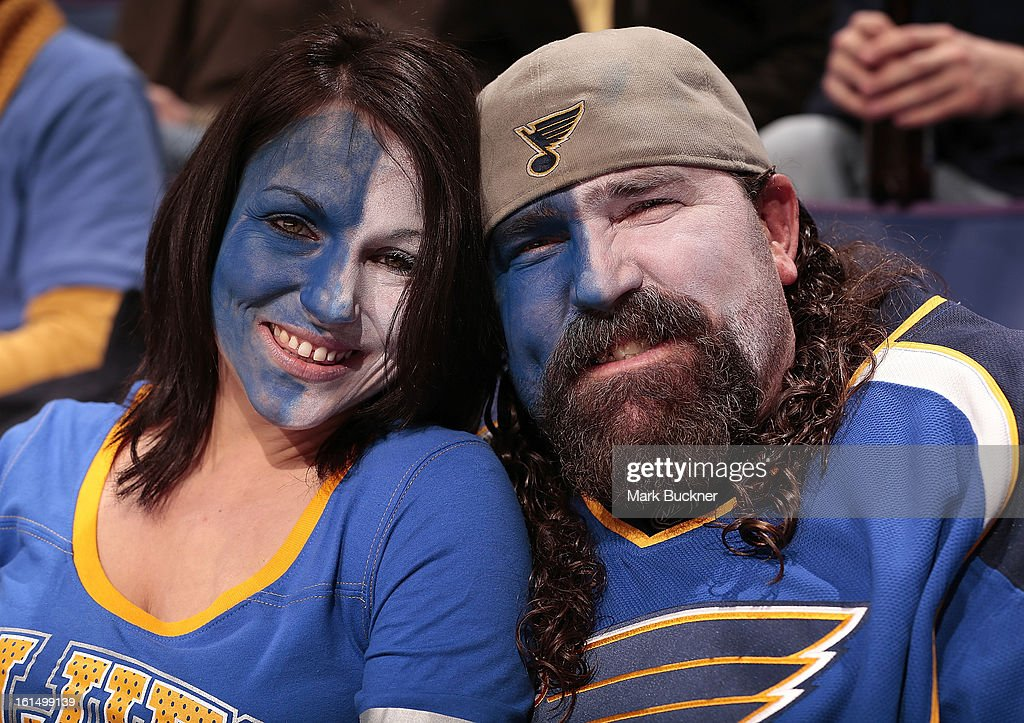Two St. Louis Blues fans enjoy the action in an NHL game between the St. Louis Blues and the Los Angeles Kings on February 11, 2013 at Scottrade Center in St. Louis, Missouri.