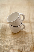 Two stacked teacups on natural burlap material