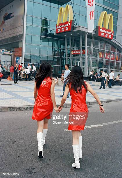 Two staff from a JVC promotion stall head for McDonald's during their lunch break They wear identical brightly coloured plastic promotional outfits...