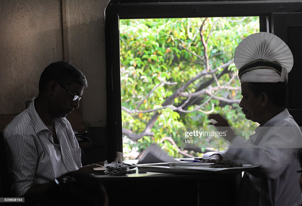 Two staff members, including a waiter with the iconoc head gear, having a discussion over a topic on May 28, 2015 in Kolkata, India.