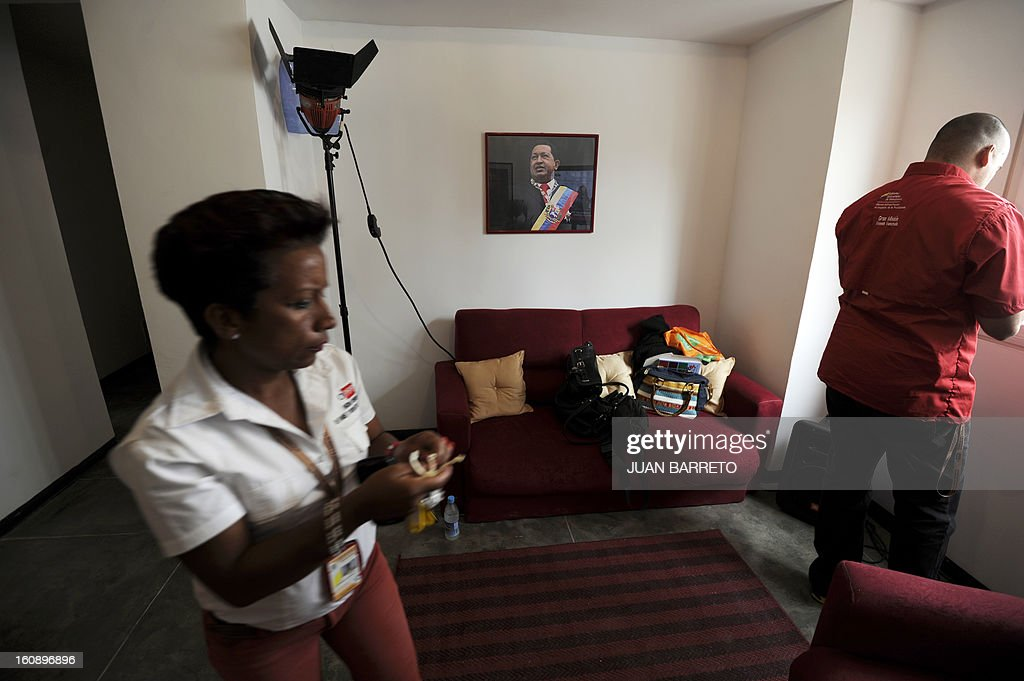 Two staffers of the Ministry for the Revolutionary Transformation of Greater Caracas give the last touches to a government-built flat before it is delivered to its new owners, in Caracas on February 7, 2013. AFP PHOTO/Juan Barreto