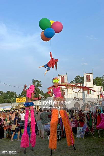 Two stilt performers and the artist Bansky with his trademark girl with balloons walk past the Chapel of love loathing in Lost Vagueness at the...