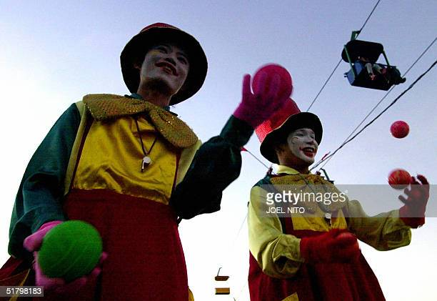 Two stilt walking clowns juggle balls while a cable car passes overhead at an amusement park in Manila 27 November 2004 Such family entertainment...