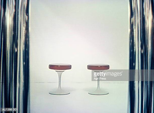 Two stools on white, framed by silver curtain (video still)