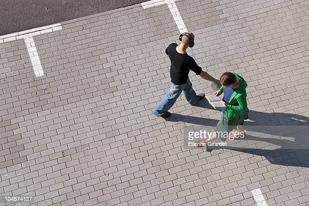 Two strangers pass each other walking through a parking lot