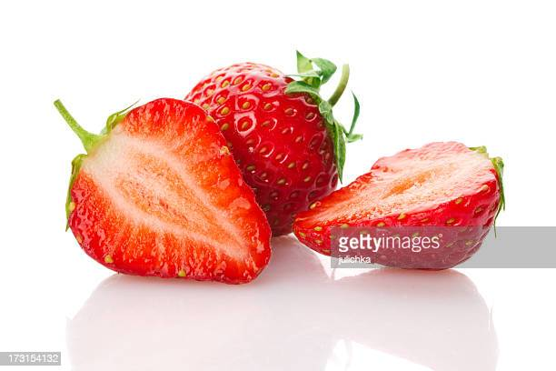 Two strawberries, one cut in half, on a white background