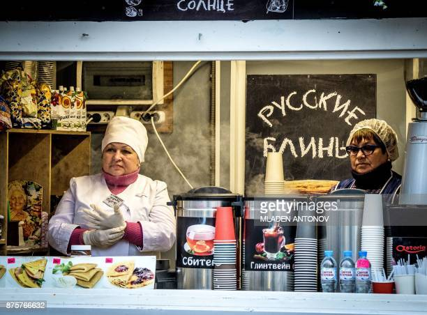 Two street vendors sell traditional Russian pancakes at Moscow's Sokolniki park on November 18 2017 / AFP PHOTO / Mladen ANTONOV