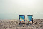 Two stripey deck chairs on beach