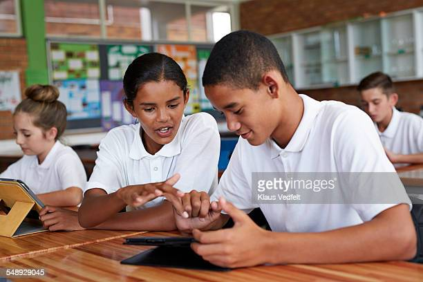 Two student working together on tablet in class