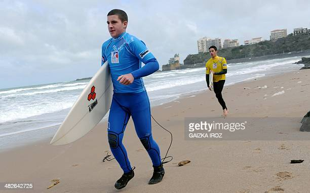 Two students carry their surfboards to the water to take their surf exam on the Cote des Basques beach in Biarritz southwestern France on April 4...