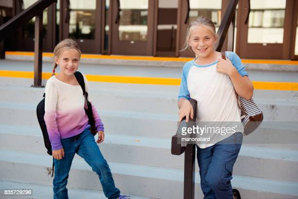 Two students girls back to school at the entrance of the school
