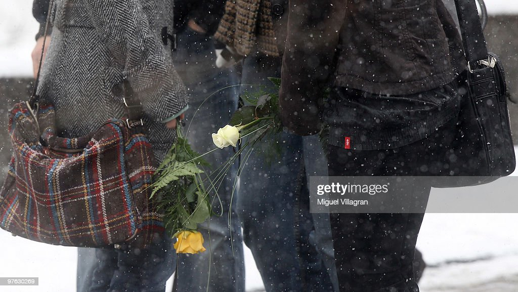 Two students hold flowers in their hands during the commemoration ceremony in front of the Albertville School on March 11, 2010 in Winnenden, Germany. Tim Kretschmer opened fire on teachers and pupils at his former school a year ago on March 11, 2009, killing 15 and leaving many more injured. Kretschmer fled the scene and shot himself dead after being cornered by police.