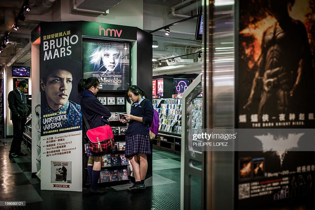 Two students listen to CDs in a HMV store in Hong Kong on January 17, 2013. Iconic British music retailer HMV is fighting for survival after slumping into administration, but its boss expressed hope the high-street giant would manage to secure its future. AFP PHOTO / Philippe Lopez