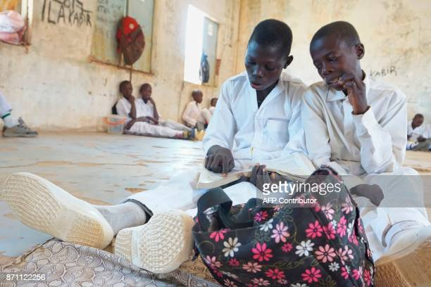 Two students sit on the floor as they revise their books at the Government Day Secondary School Muduru on November 3 2017 The 'Science on Wheels'...