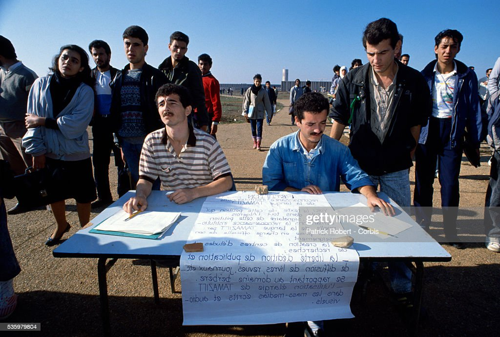Two students sit with a handwritten poster as others gather around them for a meeting at Bab-Ezzouar University in the suburbs of Algiers. Only a month before, in October 1988, hundreds of protesters, many of them students, were killed during anti-government riots.