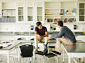 Two students sitting on desk in discussion in lab