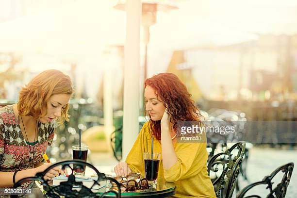 Two students studying and learning in a coffee shop